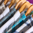 Men&#039;s shirts on hangers on purple background - Stockfoto