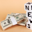 "Foto Stock: White paper cubes labeled ""News"" with money on beige background"