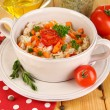 Delicious rice with vegetables and herbs in pot on wooden table close-up - Stock Photo