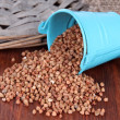 Overturned bucket with grains on wooden background — Stock Photo