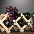Bottles of wine placed on wooden stand on grey background - Stock Photo