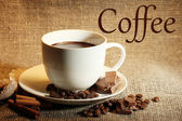 Cup of coffee and beans, cinnamon sticks and chocolate on sackcloth background — Stock Photo