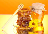 Jar of honey and honeycomb on orange background — Foto Stock