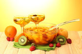 Punch in bowl and glasses with fruits, on wooden table, on yellow background — Stock Photo