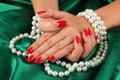 Female hands holding beads on color background — Photo