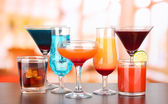 Several glasses of different drinks on bright background — Stok fotoğraf