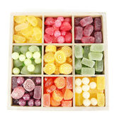 Multicolor candies in wooden box, isolated on white — Stock Photo