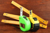 Tape measure and ruler on wooden background — Stock Photo