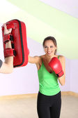 Young beautiful woman with boxing gloves at workout, at gym — Stock fotografie