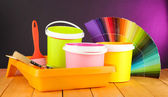 Paint pots, paintbrushes and coloured swatches on wooden table on dark purple background — Stock Photo