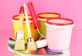 Set for painting: paint pots, brushes, paint-roller, palette of colors on pink background — Stock Photo