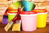 Set for painting: paint pots, brushes, palette of colors on stone wall background — Stock Photo