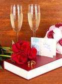 Trouwringen op bijbel met rozen en glazen van champagne op houten achtergrond — Stockfoto