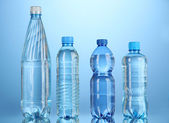 Different water bottles on blue background — Stock Photo