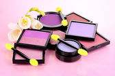 Bright eye shadows and sponge brushes for foundation on pink background — Stock Photo