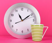 Cup tea and clock on pink background — Stock Photo