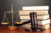 Wooden gavel, golden scales of justice and books on grey background — 图库照片