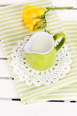 Green jug with milk on napkin on wooden picnic table close-up — Photo