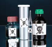 Deadly poison in bottles on black background — Stock Photo