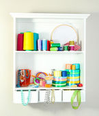 Beautiful white shelves with thread and material for handicrafts — Stock Photo