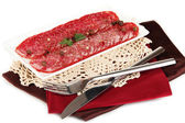 Tasty salami on plate on napkin isolated on white — Stock Photo