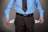 商务男人在灰色的背景上显示空口袋 — 图库照片