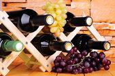 Bouteilles de vin placé sur un socle en bois sur fond de mur en pierre — Photo