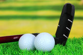 Golf balls and driver on green grass outdoor close up — Stock Photo
