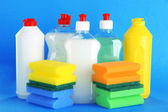 Bottles of dishwashing liquid and sponges on color background — Stock Photo