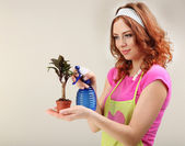 Young woman cultivating flowers on grey background — Stock Photo