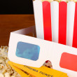 Popcorn with tickets and cinema glasses on wooden table on brown background — 图库照片