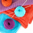 Colorful wool sweaters and balls of wool close-up — Stock Photo