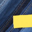 Stock Photo: Many jeans with label closeup
