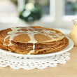 Sweet pancakes on plate with condensed milk on table in kitchen — Stock Photo