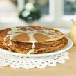 Sweet pancakes on plate with condensed milk on table in kitchen — Stock Photo #23376746