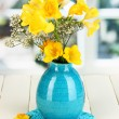Beautiful bouquet of freesia in blue vase on wooden table on window background - Stock Photo