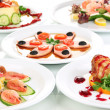 Stock Photo: Small portions of food on big white plates close up