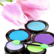 Bright eye shadows and sponge brushes for foundation close up - Stock Photo