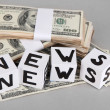"Stock Photo: White paper cubes labeled ""News"" with money on grey background"