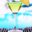 Green cocktail with lime on table on bright background - 