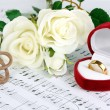 Treble clef, roses and box holding wedding ring on musical background — ストック写真