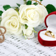 Treble clef, roses and box holding wedding ring on musical background - Стоковая фотография