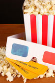 Popcorn with tickets and cinema glasses on wooden table on brown background — Stock Photo