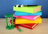 Livres de couleur avec loupe sur table sur fond bleu — Photo