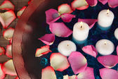 Rosenblätter und kerzen im wasser in der vase-nahaufnahme — Stockfoto