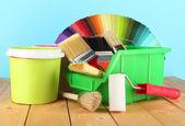 Farby garnki, pędzle i kolorowe próbki na drewnianym stole na niebieskim tle — Zdjęcie stockowe