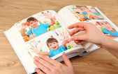 Photos in hands and photo album on wooden table — ストック写真