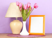 Colorful photo frame, lamp and flowers on wooden table on lilac background — Zdjęcie stockowe