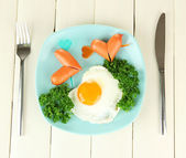 Sausages in form of hearts, scrambled eggs and parsley, on color plate, on wooden background — Stock Photo