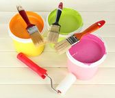 Set for painting: paint pots, brushes, paint-roller on white wooden table — Стоковое фото